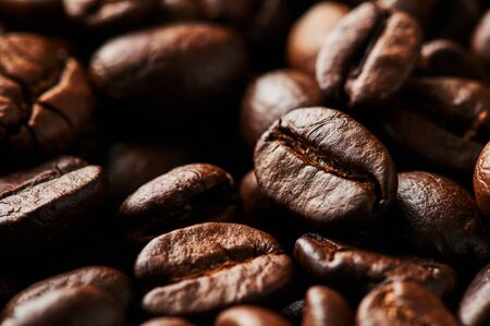 Close up of roasted coffee beans for background, texture and design. Selective focus.