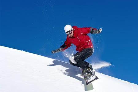 snowboard: Snowboarder jumping through air with deep blue sky in background