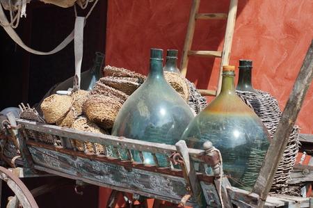 demijohn: Carboys, demijohn bottles on an old cart