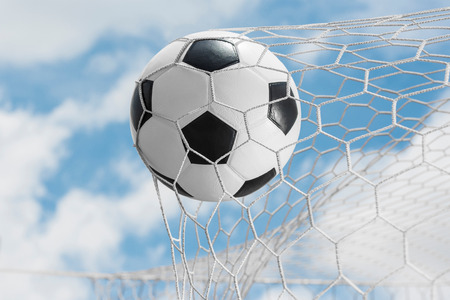 soccer net: Soccer ball kicked into the back of a goal