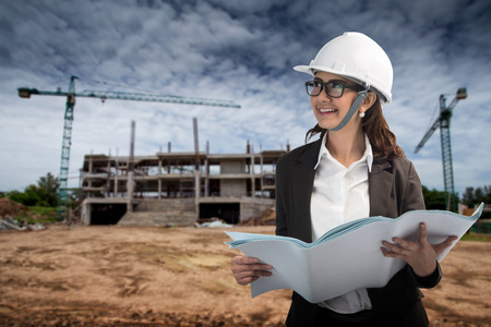 smiling girl in protective helmet with clipboard and blueprint photo