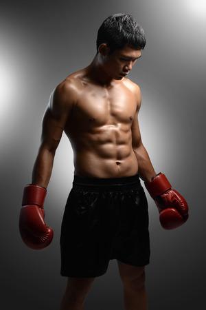 boxeador: boxeador con los guantes de boxeo de pie sobre fondo gris con focos Foto de archivo
