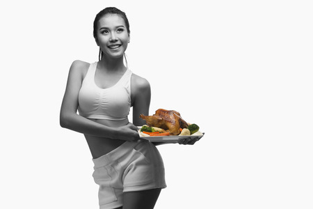 whole body: Young woman with perfect body holding and showing roast chicken for delicious menu,healthy food - healthy lifestyle concept