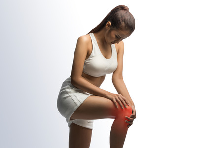 Woman having knee pain on a white background with clipping path Stock Photo