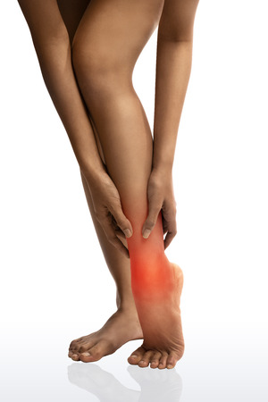 enhanced health: Acute pain in a woman ankle. Woman holding hand to spot of ankle-aches.with clipping path Stock Photo