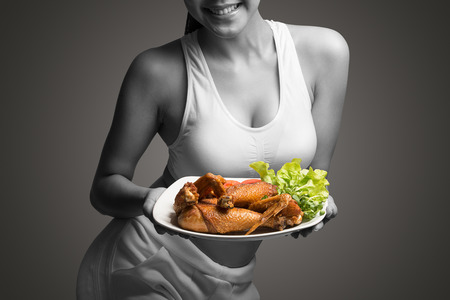 Young woman with perfect body holding and showing roast chicken for delicious menu,healthy food - healthy lifestyle concept
