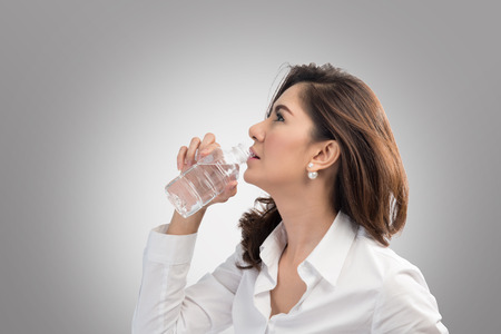 sexy office girl: Beautiful business woman drinking water from bottle on gray back ground