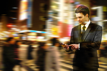 night vision: Double exposure of businessman uses the smart phone on the city street, and motion blur background Stock Photo