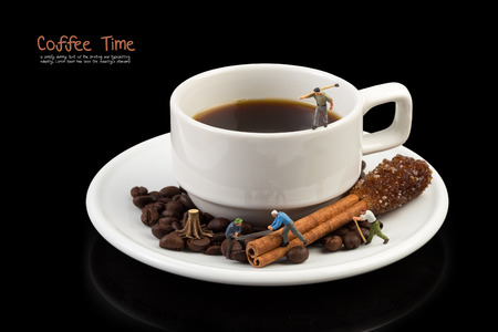 miniature man on coffee cup,coffee beans and Brown sugar on cinnamon stick,on black with clipping path