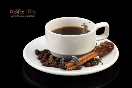 Miniatuur man op koffiebeker, koffiebonen en Bruine suiker op kaneelstok, op zwart met knippenpad