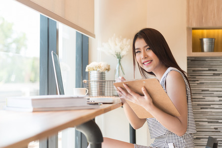 thai student: Beautiful business woman using a laptop computer and writing on business document. Stock Photo