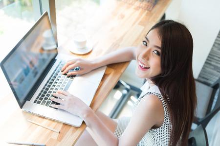 internet cafe: Hermosa mujer de negocios con un ordenador port�til Foto de archivo