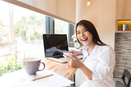 phon: Beautiful business woman using a smart phon and laptop computer Stock Photo