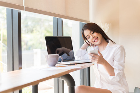 sexy secretary: Beautiful business woman using a smart phon and laptop computer Stock Photo