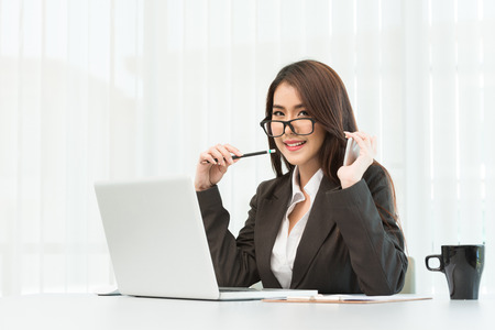 Portrait of a young business woman using smartphone and laptop at office
