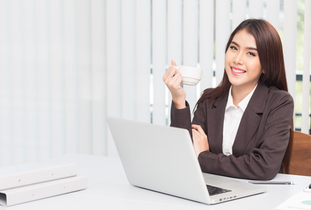 Portrait of a young business woman drinking coffee and using laptop at office