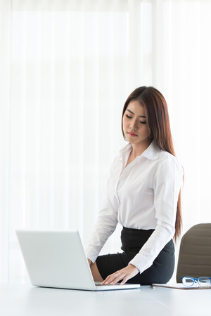 Portrait of a young business woman using laptop at office photo
