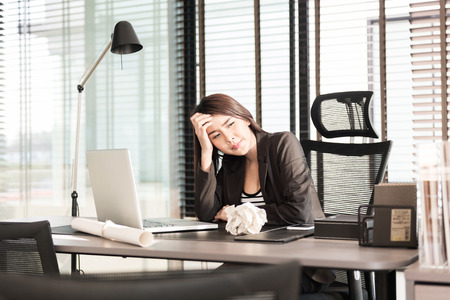 tired and sleepy young business woman at the desk with a laptop
