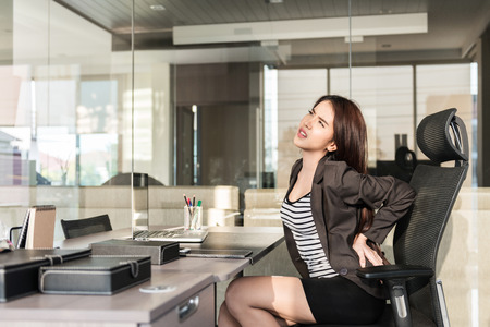 woman pain: Young businesswoman having back pain while sitting at office desk Stock Photo