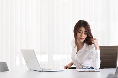 listless: Unhappy businesswoman sitting at desk