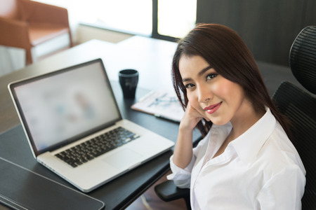 sexy business woman: Portrait of a young business woman using laptop at office