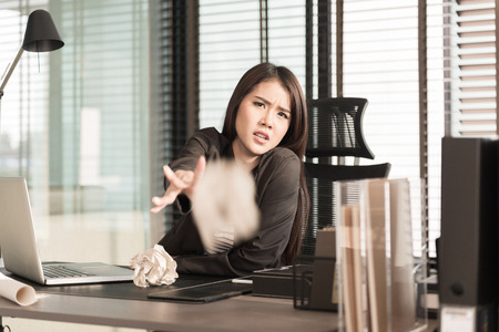 out of office: businesswoman throwing out office documents