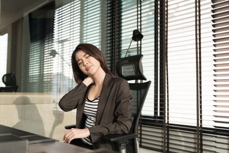 dolor muscular: Joven empresaria con dolor en el cuello sentado en el escritorio de oficina