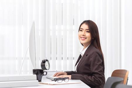 Attractive woman working in office on laptop Banco de Imagens
