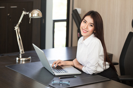 Attractive woman working in office on laptop Imagens