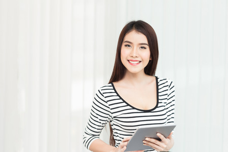 outwork: beautiful young woman on the workplace using a digital tablet