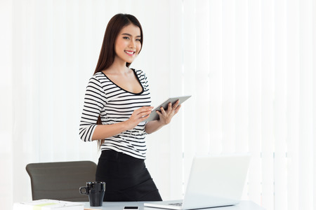 outwork: beautiful young woman on the workplace using a digital tablet and laptopclipping path