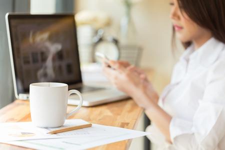 tiefe: Kaffeetasse und Geschäftsfrau, die mit Dokumenten und Laptop