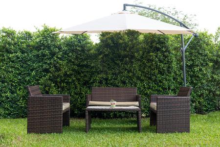 al aire libre: Conjunto de muebles de jardín de ratán bajo un gran paraguas de jardín Foto de archivo
