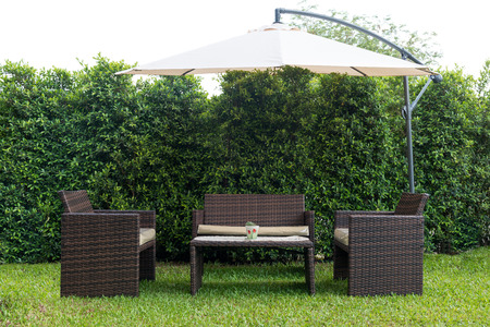 wooden furniture: Set of rattan garden furniture under a big garden umbrella