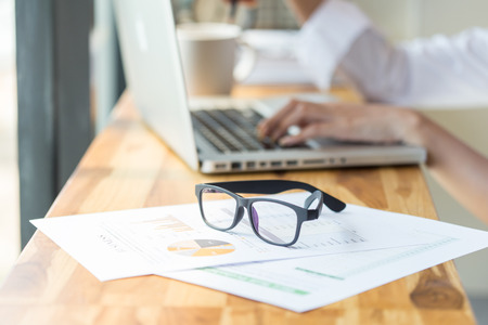 eyeglasses on wooden table with laptop
