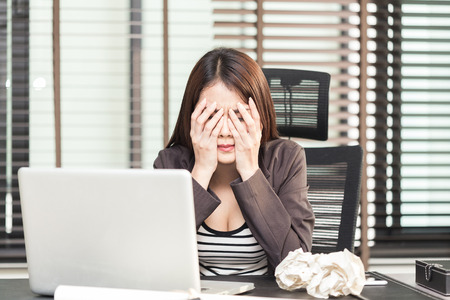 机に紙を丸めてボールに座って疲れ若い女性幹部
