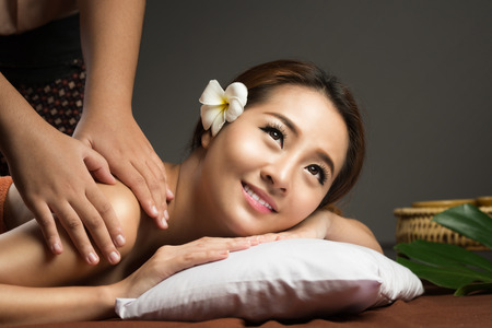spa resort: Asian woman getting thai herbal compress massage in spa. Stock Photo