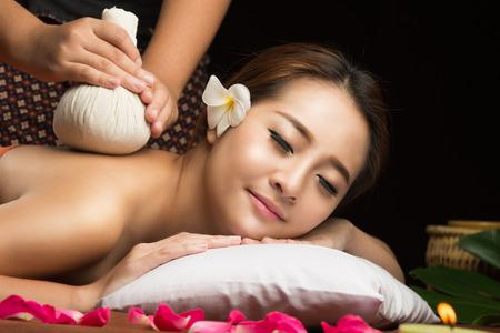 masaje: Mujer asiática recibiendo masaje tailandés compresa de hierbas en spa.She es muy relajado