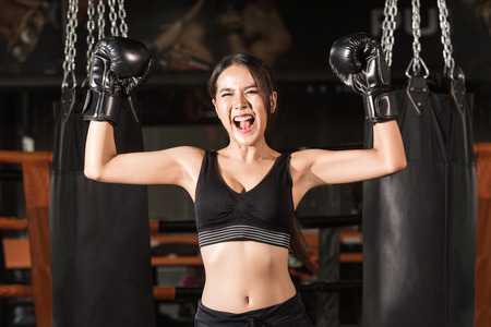 Cheerful woman in boxing gloves celebrating victory. Happy young sporty woman in boxing gloves keeping arms raised while standing at gym 写真素材