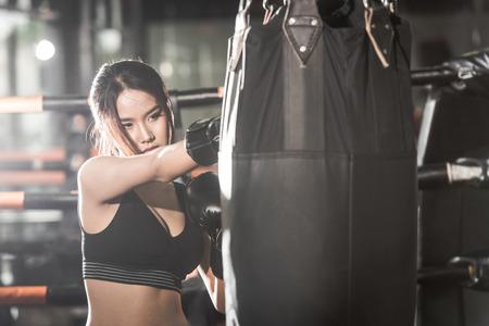 фитнес: Красивая женщина пробивая мешок с боксерские перчатки в тренажерном зале. понятие о Фитнес, спорт, боевые искусства и людей,