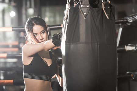 Beautiful Female Punching A Bag With Boxing Gloves at the gym. concept about sport, fitness, martial arts and people