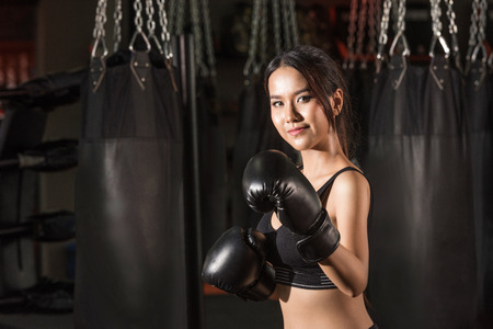 martial arts woman: Boxer woman. Boxing fitness woman smiling happy wearing black boxing gloves. Portrait of sporty fit Asian model of boxing gym