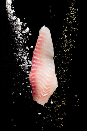 Raw Fish fillet with flour and herbs in Freeze motion on black background.