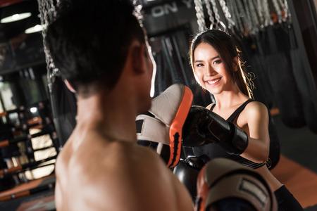 ropa deportiva: Entrenamiento de la mujer con guantes de boxeo en el gimnasio, Pareja ejercicio de perforación Foto de archivo