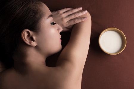 body milk: Asian woman having massage and bowl of milk , spa salon Beauty treatment