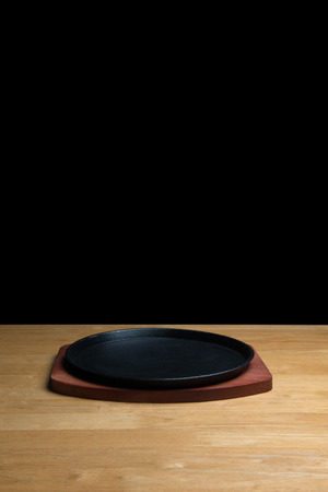 sizzling: Cast Iron Sizzling Steak Plate on wooden table,black background