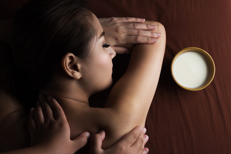 body milk: Asian woman having massage and bowl of milk , spa salon Beauty treatment