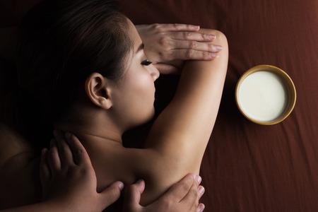 masajes relajacion: Mujer asiática que tiene masaje y el cuenco de leche, balneario del salón Tratamientos de belleza Foto de archivo