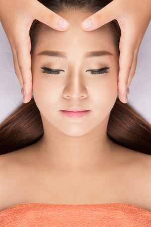 Asian woman in spa gets a facial massage