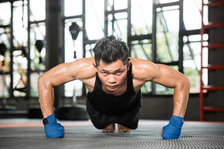 Attractive muscular man doing push-ups on gym floor